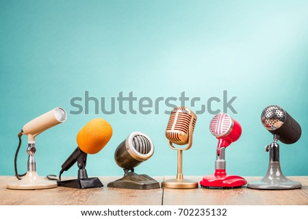Retro old microphones for press conference or interview on table front gradient aquamarine background. Vintage old style filtered photo Stockfoto ©