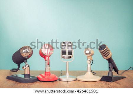 Retro old microphones for press conference or interview on table. Vintage style filtered photo