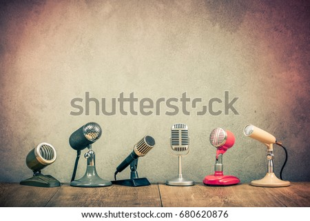 Retro old microphones for press conference or interview on wooden desk. Vintage instagram style filtered photo Stockfoto ©
