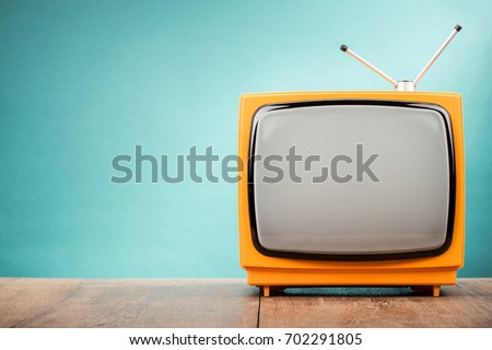 Photo of  Retro old orange TV receiver on table front gradient aquamarine wall background. Vintage style filtered photo