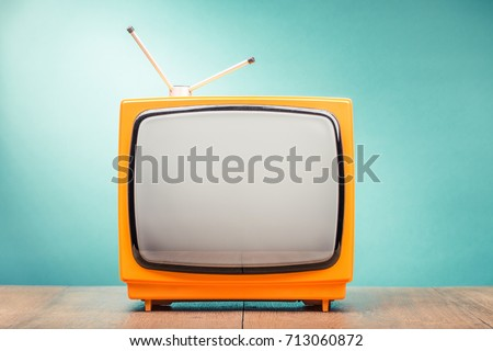 Retro old orange TV set receiver on wooden table front gradient mint green wall background. Vintage instagram style filtered photo