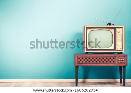 Retro old outdated classic television receiver with TV antenna from circa 60s of XX century on wooden stand with amplifier front gradient mint blue wall background. Vintage style filtered photo stock photo