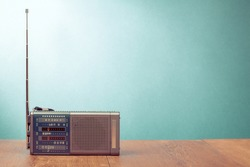 Retro old radio receiver on table front  mint green background