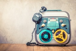 Retro old reel to reel tape recorder and headphones front concrete wall background. Vintage instagram style filtered photo