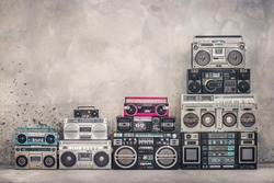 Retro old school design ghetto blaster boombox stereo radio cassette tape recorders tower from circa 1980s front aged concrete wall background. Vintage style filtered photo