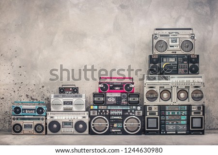 Retro old school design ghetto blaster boombox stereo radio cassette tape recorders tower from circa 1980s front aged concrete wall background. Vintage style filtered photo #1244630980