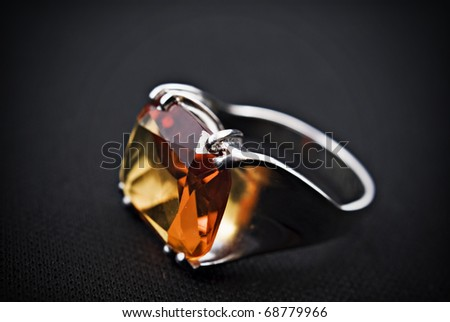 retro old silver ring with orange gem on black background