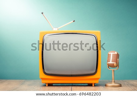 Retro old TV receiver and golden microphone on table front gradient mint green wall background. Broadcasting concept. Vintage style filtered photo