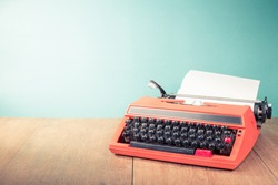 Retro old typewriter with paper sheet on wooden table front mint green background. Vintage style filtered photo