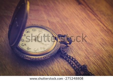 Retro old watch on the wood texture background vintage color tone