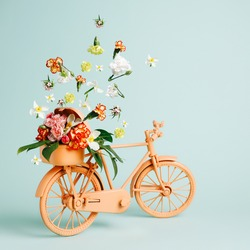Retro orange bicycle with flowers flying out of basket against pastel green background. Creative flower delivery concept. Florist or spring bloom banner with copy space. Natural romantic card.