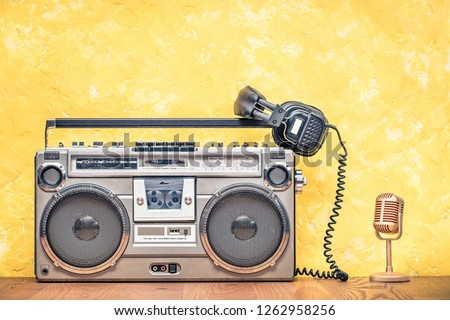 Retro outdated portable stereo boombox radio cassette recorder from circa late 70s, golden microphone and aged headphones front textured yellow wall background. Vintage old style filtered photo
