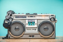 Retro outdated portable stereo boombox radio cassette recorder from circa late 70s with aged headphones front aquamarine wall background. Listening music concept. Vintage old style filtered photo
