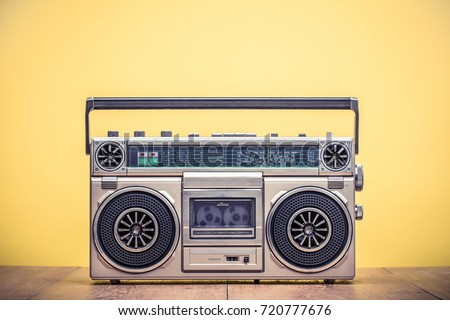 Photo of  Retro outdated portable stereo boombox radio cassette recorder from 80s front yellow background. Vintage instagram old style filtered photo