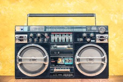 Retro outdated portable stereo boombox radio receiver with cassette recorder from circa 80s front concrete textured yellow wall background. Listening music concept. Vintage old style filtered photo