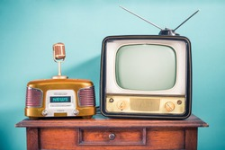 Retro outdated TV set from 60s, old FM radio, golden microphone on oak wooden table front mint blue background. News, press conference or nostalgic music concept. Vintage style filtered photo