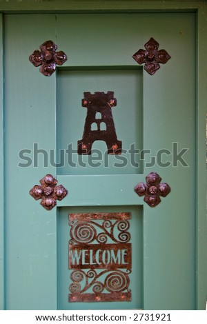 "Retro painted door with rusty metal decoration and ""Welcome"" sign"