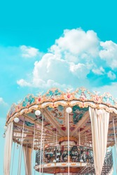 Retro pastel colorful Children's merry-go-round at the amusement park in the blue sky  and fluffy cloud background like in the heaven.