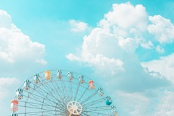 Retro pastel colorful ferris wheel of the amusement park in the blue sky  and cloud background.