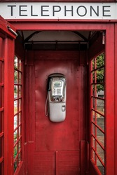 retro payphone in a red telephone box