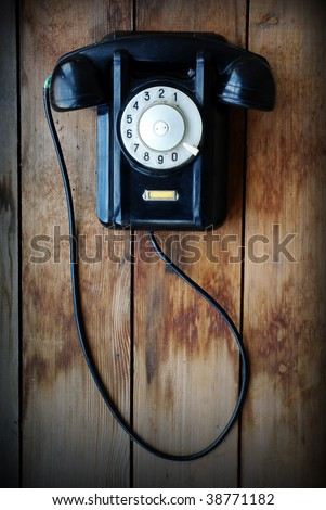 Retro phone on a wooden wall - stock photo