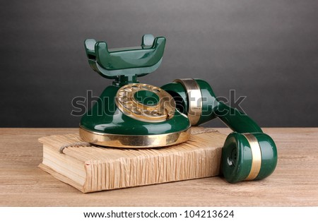 Retro phone standing on book on wooden table on grey background