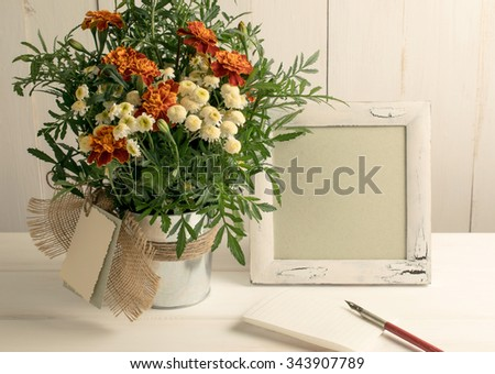 Retro photo frame and old pen with sheet paper and tagetes bouquet on wooden board in shabby chic style
