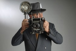 Retro photo journalist wearing a Fedora hat and holding a vintage camera with flash bulb