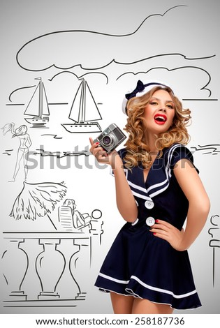Retro photo of a glamorous pin-up sailor girl posing and taking a photo of a seashore and tourists with an old vintage photo camera on grey sketchy background. #258187736