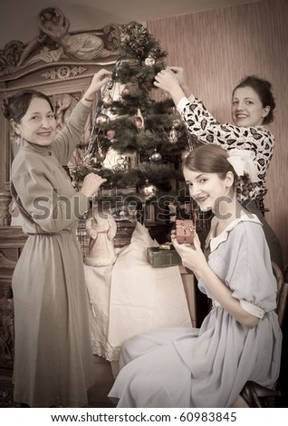 Retro photo of  daughters with mother decorating Christmas tree at home