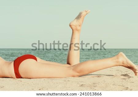 Retro Photo Of Girl Relaxing Her Feet On The Ocean Beach