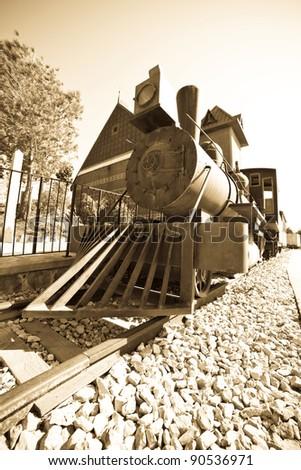 Retro photo of old steam locomotive at railway station