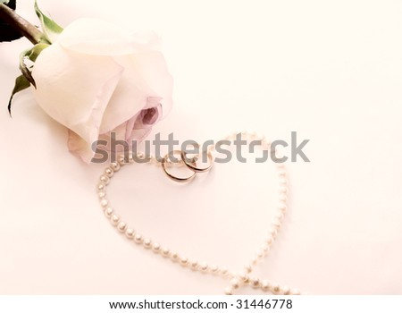 Retro picture of a rose, wedding rings, pearl necklace in the shape of heart