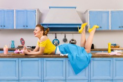 Retro pin up girl woman female housewife wearing yellow top, blue skirt and white apron lying relaxing with lollipop on kitchen with utensils and tray with pink milkshake and cupcakes. Retro styled
