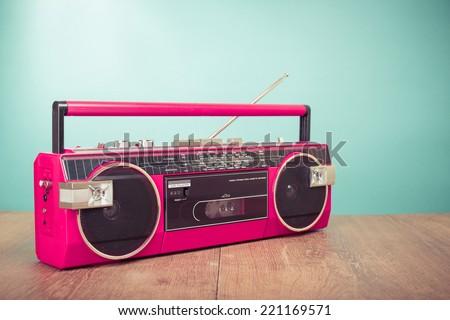 Retro pink radio cassette stereo recorder on wooden desk
