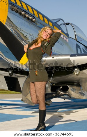 retro pinup girl in army uniform standing next to a world war two aircraft and smiling