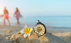 retro pocket watch and plumeria flower on sand beach, blurred tropical background. Summer relax. travel, adventure and sea trip vacation concept.