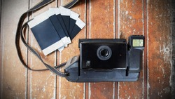 Retro Polaroid Camera With Polaroid Film on Old Wooden Table, Top View, Empty Space For Text