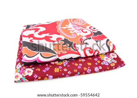 Retro polyester textiles with floral patterns in red. Isolated over white background.