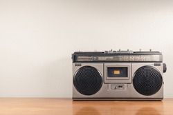 Retro portable radio on the table and concrete wall as space for text, outdated stereo boombox with cassette player
