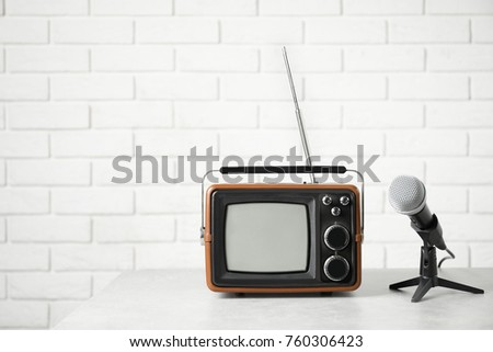 Retro portable TV and microphone on table against brick wall #760306423