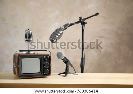 Retro portable TV and microphones on table against light wall #760306414