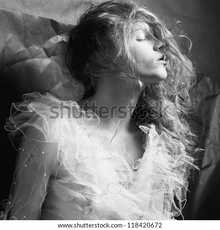 Retro portrait of a dreaming queen like girl over wrinkled black paper background. black and white studio shot
