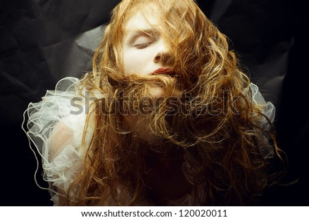 Retro portrait of red-haired (ginger) queen like girl over wrinkled black paper background. studio shot