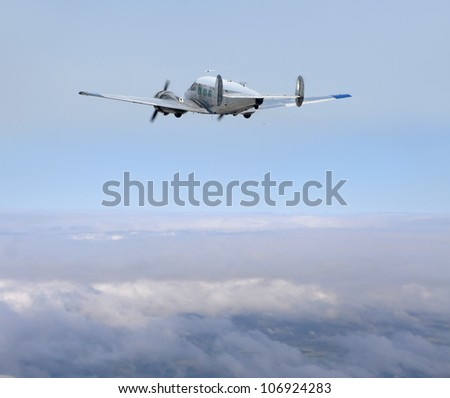 Retro propeller airplane flying high above the clouds