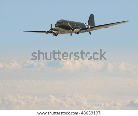 retro propeller airplane high above the clouds