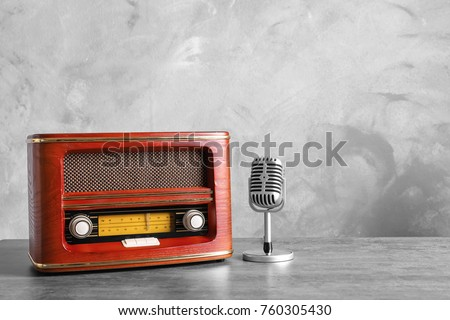Retro radio and microphone on table against light wall