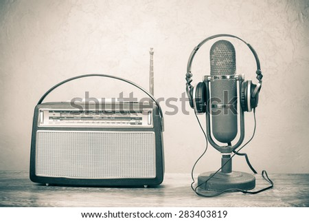 Retro radio from 60s, old ribbon studio microphone and headphones. Vintage style sepia photo