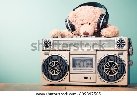 Retro radio recorder and toy Teddy Bear with headphones in front mint background. Vintage style filtered photo