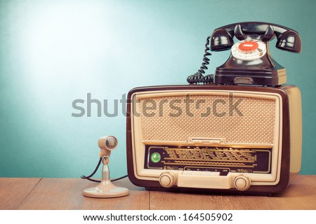 Retro radio with green light, microphone and telephone on wooden table
